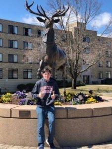Michael Riggi standing in front of deer statue.
